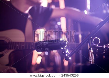 the man plays the drums, the game is on the working drum with sticks close-up. On the background of colored lights. Musical concept with a working drum. stock photo