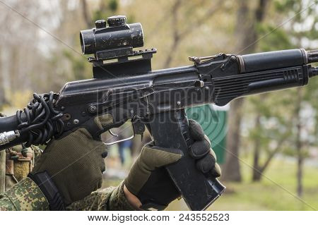 man aiming with an AK-47 with reflex sight, separatist. Male mags in the Kalashnikov. reloading the rifle. clip replacement. Practice shooting. Training in the army. Training soldiers stock photo