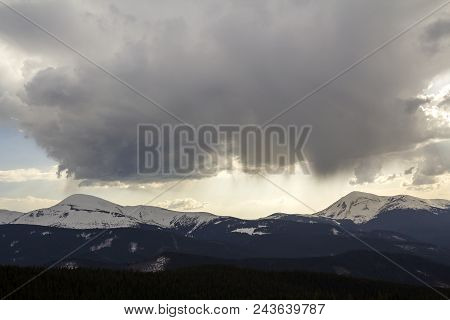 Fantastic view of huge white dark foreboding stormy cloud covering blue sky low over mountains Hoverla and Petros in Carpathian mountains range with bright snow on tops. Beauty and power of nature. stock photo
