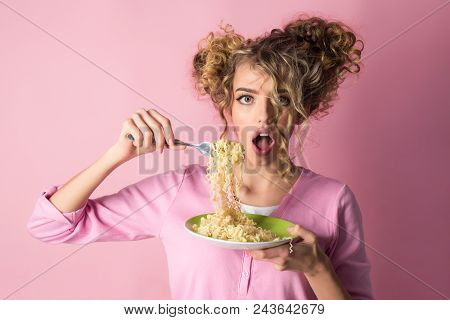 Fashion girl eating noodles. Female hold plate of spaghetti. Morning breakfast - attractive woman eating macaroni. Adorable woman with curly hair eating pasta. Fashion, beauty, diet, food, meal, italy stock photo