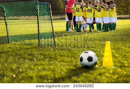 Soccer football training for young boys. Training session on the grass soccer field. Soccer ball and pylon cone and soccer goal in the foreground. Youth football team standing together with coach stock photo