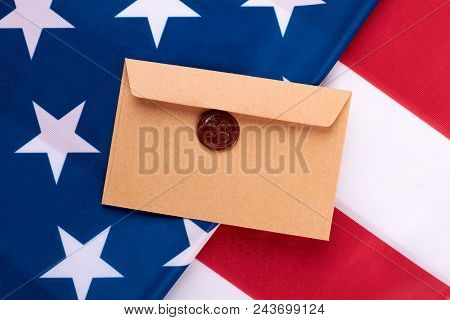 Brown envelope with stamp on American flag. American flag background with vintage style postal envelope. Greeting with National Day of USA. stock photo