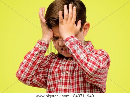 Handsome toddler child with green eyes terrified and nervous expressing anxiety and panic gesture, overwhelmed over yellow background stock photo