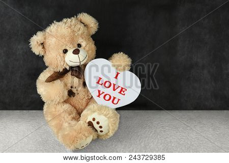 Teddy bear with red hearts wishes you a happy Valentine day stock photo