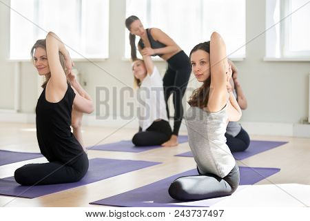 Young female yoga instructor teaching Mermaid pose, Eka Pada Rajakapotasana exercise for a group of sporty people practicing in studio, working out indoor, teacher helping to master, full length stock photo