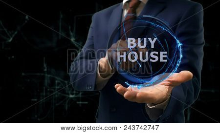 Businessman shows concept hologram Buy house on his hand. Man in business suit with future technology screen and modern cosmic background stock photo