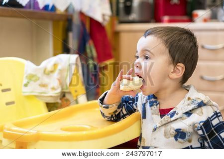 Funny boy 2 years with a banana in his mouth. Boy 2 years old eating banana. Baby 2 years old eating a banana in the kitchen. stock photo