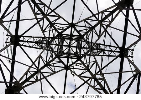 symmetrical pattern formed by a bottom view of a steel grid-shaped power line support stock photo
