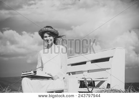 Happy journalist. Happy girl in wreath and white dress on bench. Assistant or secretary working on nature on sunny day. Summer vacation concept. Vintage equipment and archaism. Woman typing on typewriter on cloudy sky. stock photo