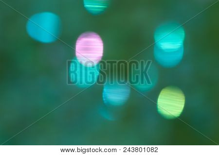 Bokeh background. Dark green blue background with blurred stripy spheres in bright turquoise blue, pink and green. Irregular pattern. stock photo