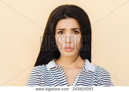 Gloomy brunette young female pouts lips in discontent, being dissatisfied with something, has healthy pure skin, dark eyes and make up, dressed in casual clothes, isolated over studio background stock photo