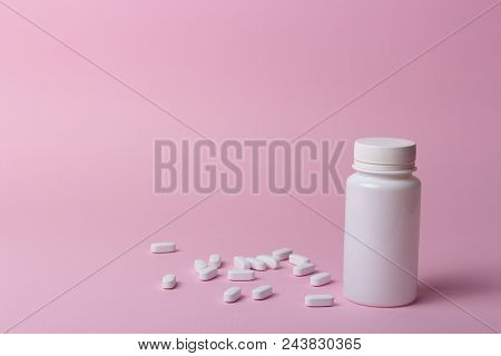 one white pill bottle on pink background. storage pills. vitamins. release pills. and white pills, pills lie next to each other. stock photo
