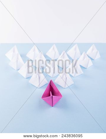 One Unique Pink Paper Boat among Many Ones. Different Paper Ships as Individuality and Leadership Concept stock photo