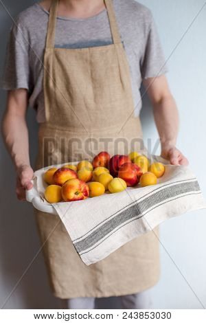 A man is holding a tray fukk of fresh apricots and peaches from the garden. stock photo