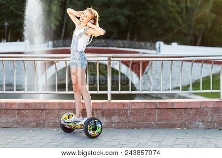 Happy girl riding on hover board or gyroscooter outdoors at sunset in summer. Active life concept stock photo