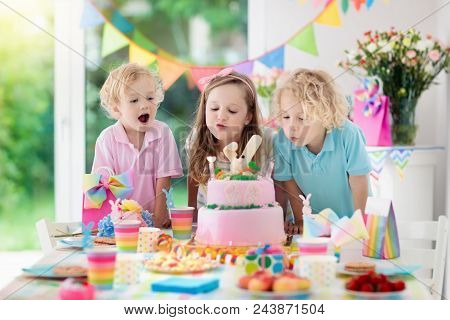 Kids birthday party. Children blow out candles on pink bunny cake. Pastel rainbow decoration and table setting for kids event, banner and flag. Girl and boy with birthday presents. Family celebration. stock photo