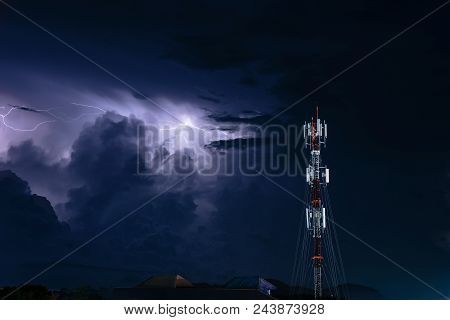 Thunderstorm with lightning over the cell phone antenna tower at night stock photo