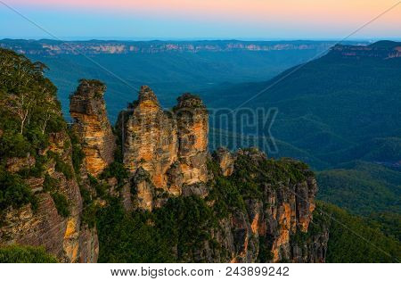 Three Sisters landmark in front of a backdrop of the Blue Mountains landscape just after sunset in NSW, Australia stock photo