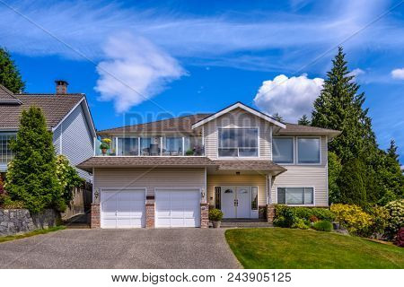 A perfect neighborhood Houses in suburb at Summer in the north America. Fragment of a luxury house with nice window over blue sky. stock photo