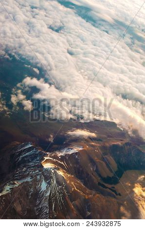 Dreamlike view of many white fluffy clouds at sunrise in warm yellow light. Blue sky on the horizon. Air travel on a sunny cloudless day. Feeling of wonder and splendor stock photo