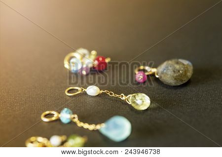lemon quartz, ruby, pearl,labradorite,apatite, green chalcedony, blue topaz necklace charm isolated on black background.close up. stock photo