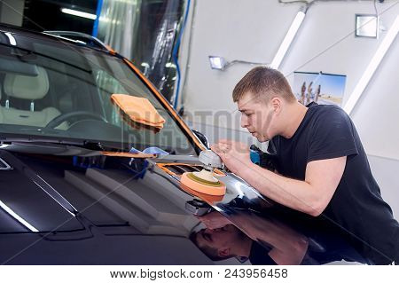 A man is polishing a blue car. Polishing machine and polishing paste for gloss. stock photo