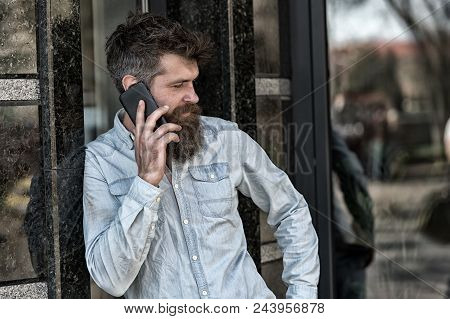 Man with beard and mustache on strict face talking, building on background. Bearded man speaking on cell phone. Communication concept. Hipster with beard speak on mobile phone outdoor. stock photo