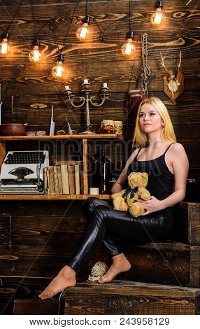 Girl in black clothes holds teddy bear toy in hand, wooden interior on background. Woman on dreamy face relaxing in wooden interior. Lady blonde enjoy leisure with teddy bear. Rest and relax concept. stock photo