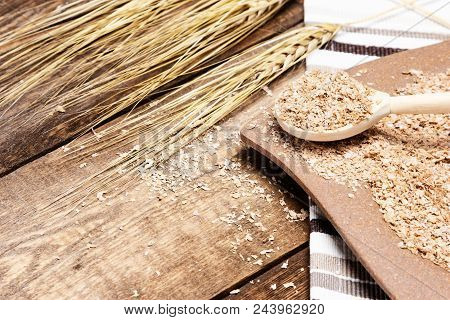 Plate and wooden spoon filled with wheat bran next to wheat ears on wood table. Healthy eating concept stock photo