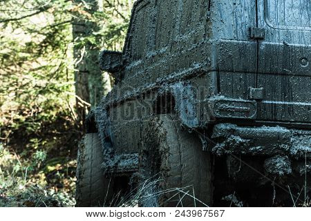 Offroad car on sunny natural background. Tires, doors, windows and mirror covered with lot of mud. Fragment of dirty suv during offroad race. 4x4 racing concept. stock photo