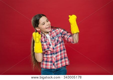 Cause dirt happens. Happy child wear rubber gloves red background. Little housemaid. Household activity. Household cleaning products. Providing household help. Enjoying household routines. stock photo