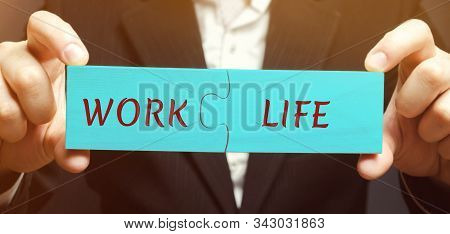 A man collects wooden puzzles with the words Work and Life. The concept of paying attention to the life values, promotion at work. Right balance. Harmony. Time management stock photo