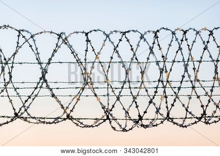 W rapped barbed wire fence with spikes and sky in the background. Rusted chain link fence guarding high security facility like airport, jail or country boarder stock photo