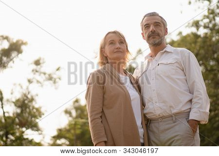 Senior elegant caucasian couple looking determine toward the happy retirement life in the park with copy space and afternoon sunlight, happily retired spouse, well-managed retirement life concept. stock photo