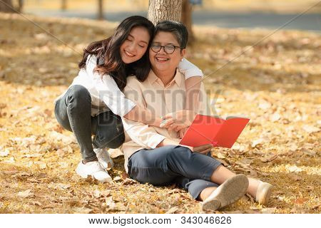 Beautiful Asian mature mother and adult daughter spend a good time together in the park while the daughter embrace her mother from behind and smiling with love, concept mother-daughter, mother's day. stock photo