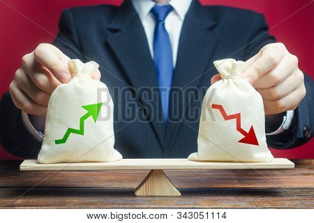 A businessman estimates the ratio of income to expenses. Profitability and return on investment and business summary. Profit and costs. Trade balance. Financial profit. Fund management stock photo