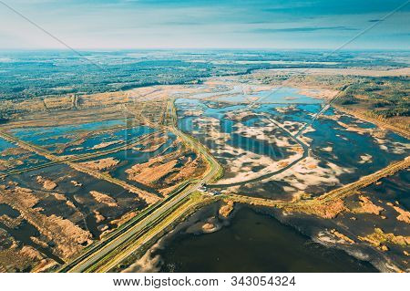 Belarus. Aerial View Of Road Through Ponds In Autumn Landscape. Ponds Of Fisheries In The South Of Belarus. Top View Of Fish Farms From High Attitude. Drone View. Birds Eye View. stock photo