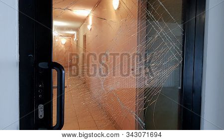 Broken glass front door windows of apartments of a residence seen from the street. Made with hammer by thief. Vandalism, insurance, alarm concept. stock photo