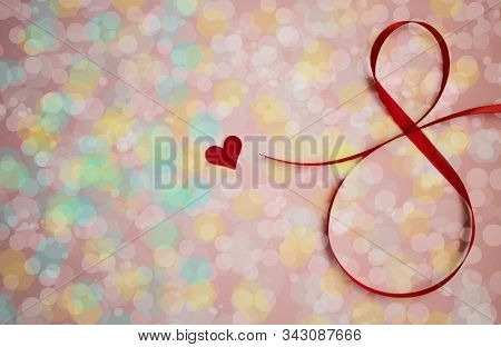 red ribbon with bokeh effect. Red heart with bokeh effect, layout for the holiday on March 8, bokeheffect for the 8 March holiday stock photo