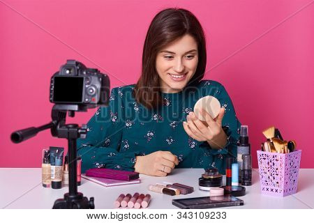 Useful beauty blog. Nice attractive brunette woman giving advice about cosmetics while having her beauty blog, holding handy mirror in hands, female posing isolated over pink studio background. stock photo