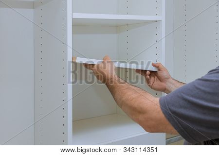 Assembling shelves with home a new apartment installing wooden shelves on wall stock photo