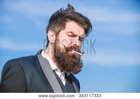 Truth about smoking pleasure and nicotine addiction. Bearded hipster smoking cigarette blue sky background. Guy with cigarette enjoy nicotine influence. Man with beard and mustache hold cigarette stock photo