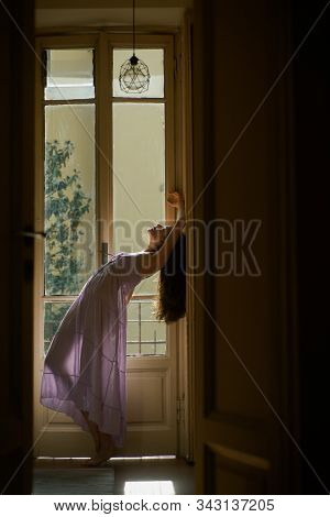 Young woman enjoying being alone. Girl meets morning near balcony. Concept of beauty.  young woman in nightie in dance stock photo
