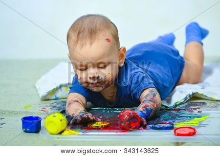Happy baby child draws with colored paints hands. Happy child draws. Beautiful baby covered in bright paint. Painted in skin hands. Copy space. Early learning. White background stock photo