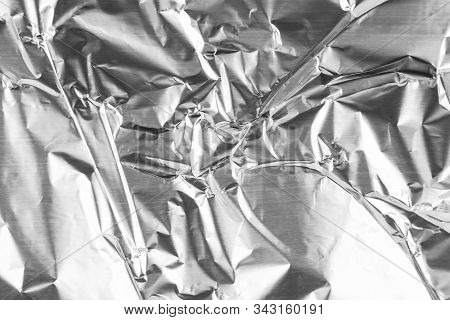 Close up of aluminium foil crumpled. Silver aluminium foil texture background. Abstract metallic paper pattern. Texture of crumpled aluminum kitchen foil. Silver abstract background stock photo