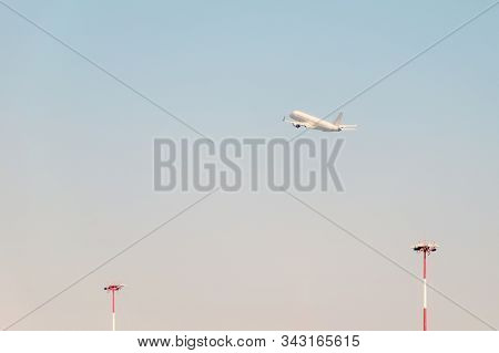 Plane is gaining altitude in the sky against the background of radar antennas. Vintage soft toning. Travel background. stock photo
