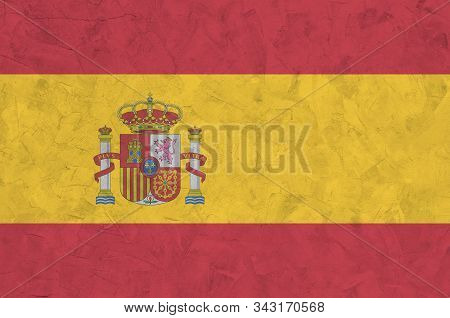 Spain flag depicted in bright paint colors on old relief plastering wall. Textured banner on rough background stock photo