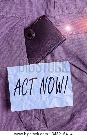 Text sign showing Act Now. Conceptual photo fulfil the function or serve the purpose of Take action Do something Small little wallet inside man trousers front pocket near notation paper. stock photo