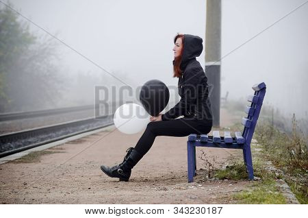 Lonely girl in black clothing sits on a bench on a railway platform in a fog. She holds a black and white balloon in her hands and thinks. The concept of choice, good and evil stock photo