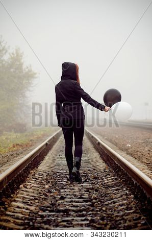 Lonely girl in black clothing walking between the rails in a fog. She holds a black and white balloon in her hands and loking at it. Concept of choice, good and evil stock photo